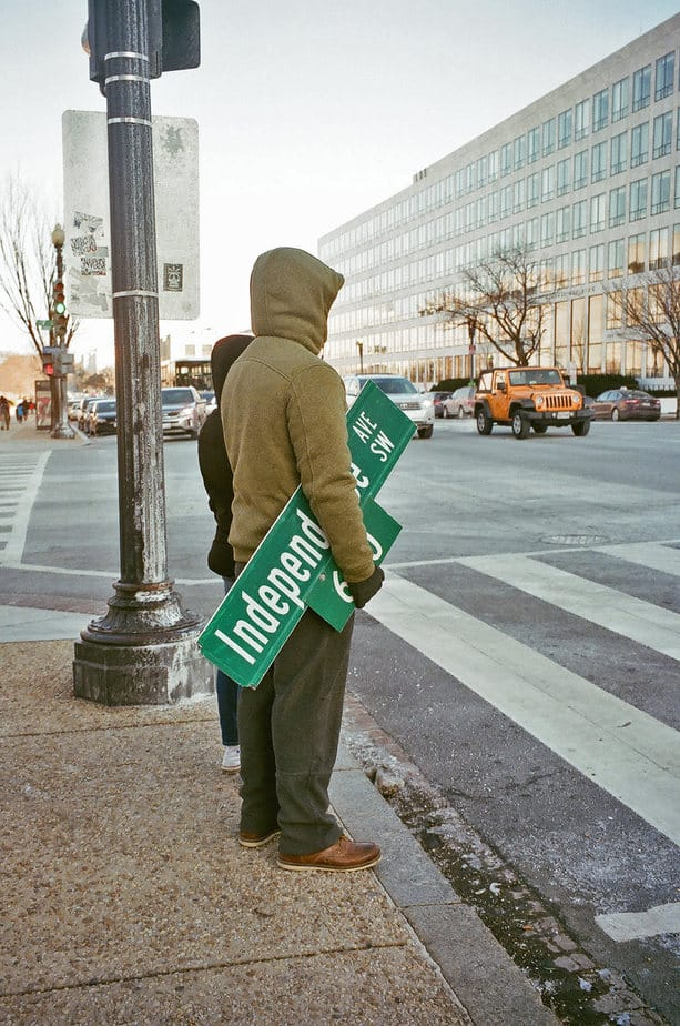 hooded man carrying an Independence Street sign
