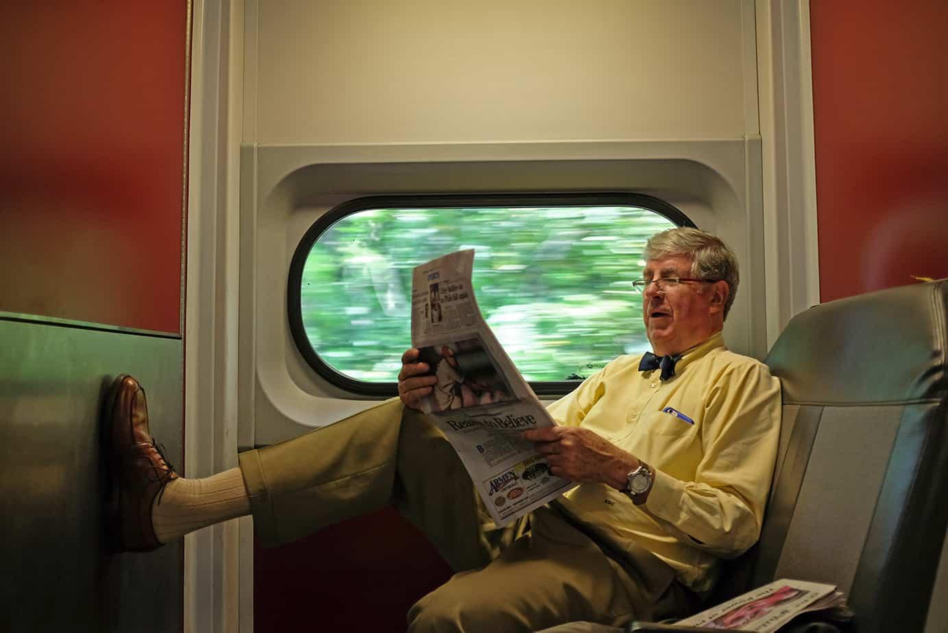man riding train, reading a newspaper