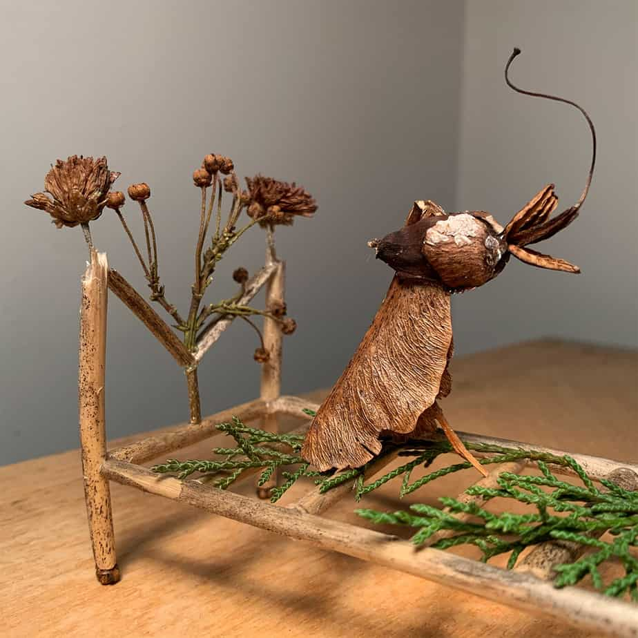 sculpture of birds in a bed made out of twigs and leaves